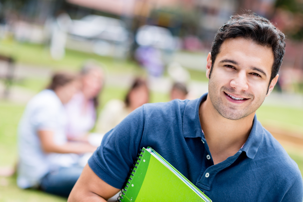 Happy male student holding a notebook and smiling